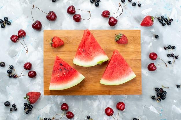 Een bovenaanzicht verse watermeloen gesneden en zacht op bruin houten rond fruit op helder Gratis Foto
