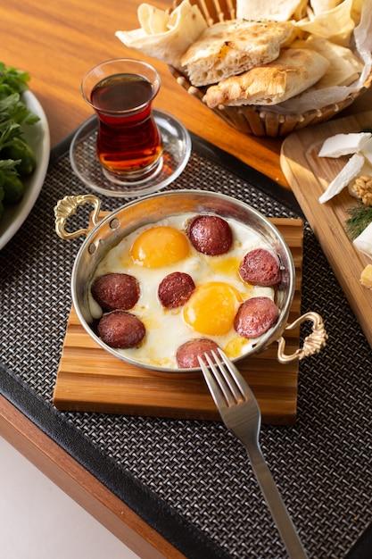 Een bovenaanzicht worst met eieren samen met thee en brood op de tafel van het restaurant eten maaltijd ontbijt Gratis Foto