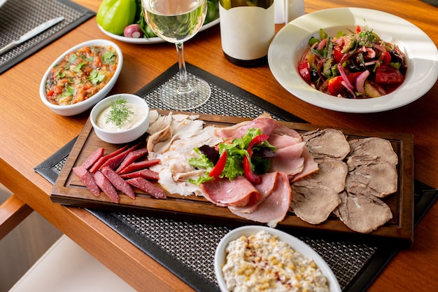 Een bovenaanzicht worstjes op bureau met witte wijn en groenten op tafel eten maaltijd restaurant vlees Gratis Foto