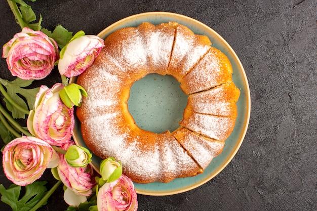 Een bovenaanzicht zoete ronde cake met suiker poeder op de top gesneden zoete heerlijke geïsoleerde binnenkant plaat samen met bloemen en grijze achtergrond koekje suiker koekje Gratis Foto