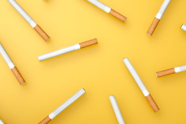 Een bovenste afbeelding van verschillende sigaretten. plat leggen. sigaretten op geel. Premium Foto