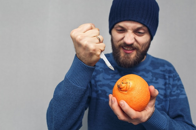 Een boze, bebaarde man wil met een scalpel de navel van een sinaasappel uitsnijden. concept van problemen als gevolg van aambeien. Premium Foto