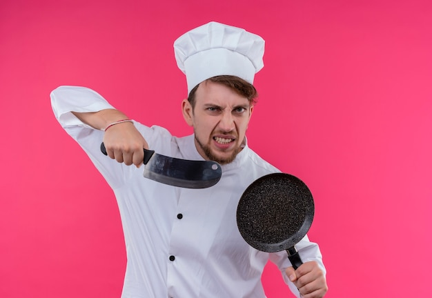 Een boze jonge, bebaarde chef-kokmens in wit uniform die vleesmes met koekenpan houdt terwijl hij op een roze muur kijkt Gratis Foto