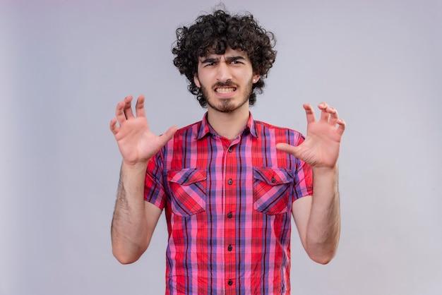 Een boze knappe man met krullend haar in een geruit overhemd die een klauwgebaar doet als een kat Gratis Foto