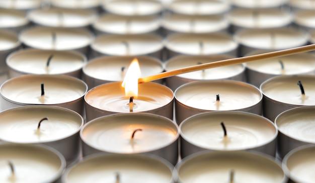 Een brandende kaars en veel gedoofde kaarsen Gratis Foto