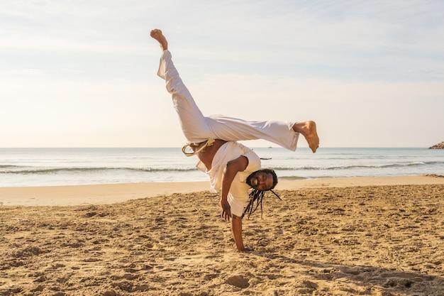 Een braziliaanse man traint capoeira op het strand. - concept over mensen, levensstijl en sport. een jongen voert de schop in de sprong uit. Premium Foto