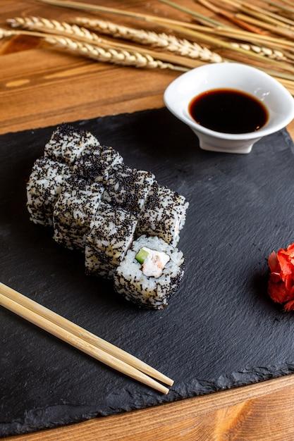 Een broodje van vooraanzichtvissen vulde met gesneden groentenrijst samen met de zwarte vissen japan van de sausmaaltijd Gratis Foto