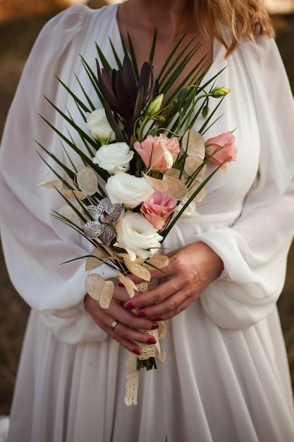 Een bruid in een witte trouwjurk houdt een delicaat bruidsboeket rozen en veel groen vast. stijlvol huwelijksboeket op een zonsondergangachtergrond Premium Foto