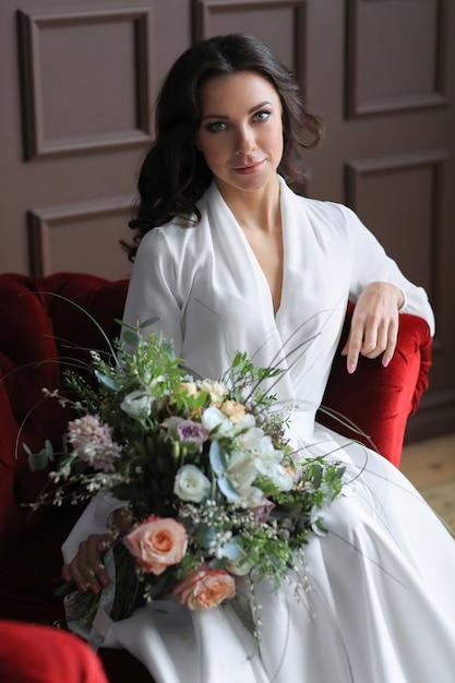 Een bruid in trouwjurk zittend op de rode bank met een bloemboeket Gratis Foto
