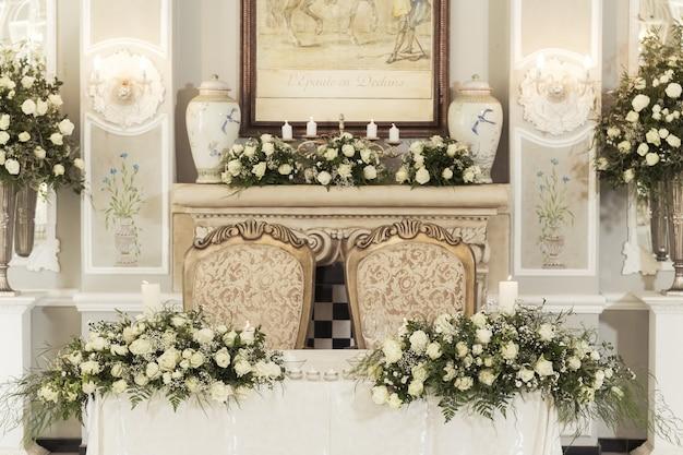 Een bruiloft tafel instelling met florale decoraties en kaarsen met hangende lampen Gratis Foto
