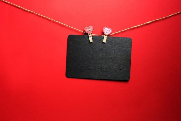 Een bruin houten schrijfbord met copyspace hangt aan een touw met twee wasknijpers met hartjes en het opschrift love. valentijnsdag, mock-up voor geliefden. rode achtergrond, frame Premium Foto