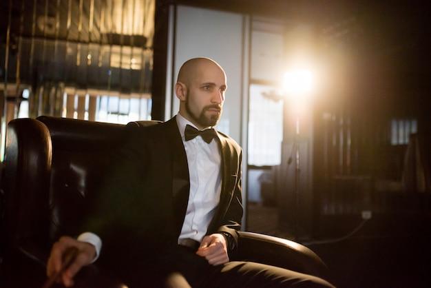 Een brutale man in een jasje rookt een sigaar. Premium Foto