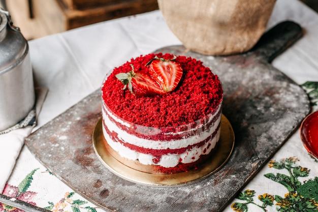 Een cake van het vooraanzicht rode die fruit met aardbeien wordt verfraaid rond met room heerlijke zoete verjaardagsviering op het bruine bureau Gratis Foto