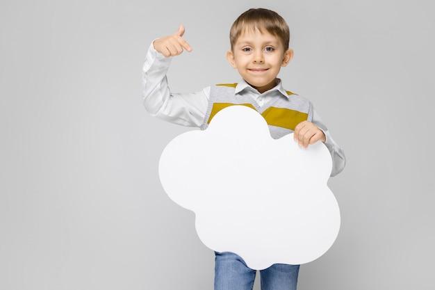 Een charmante jongen in een wit shirt, gestreepte tanktop en lichte jeans staat op een grijze achtergrond. de jongen houdt een witte poster in de vorm van een wolk vast Premium Foto