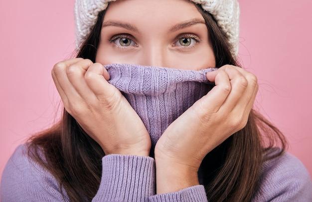 Een charmante vrouw met donker golvend haar met grote groene ogen bedekte haar lippen en neus met een keeltrui Premium Foto