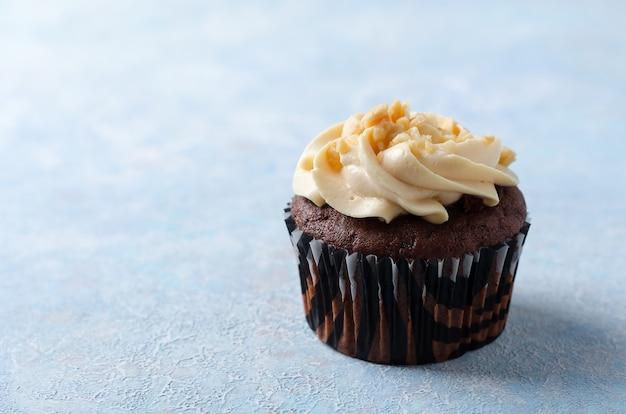 Een chocolade cupcake met karamel crème en pinda's op een blauwe achtergrond. Premium Foto