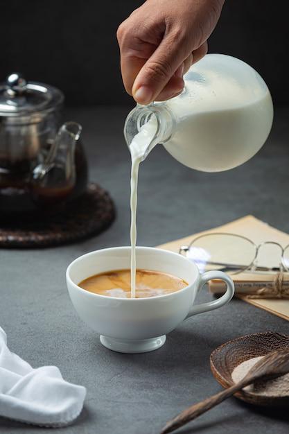 Een close-up van een hand die koffiewater giet in een koffiekop, internationaal koffiedagconcept Gratis Foto
