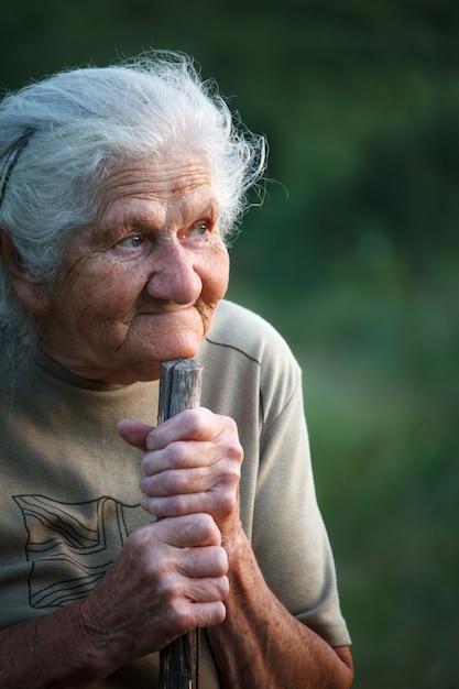 Een close-upportret van een oude vrouw met grijs haar die glimlacht en omhoog kijkt, haar kin op een stok laat rusten alsof ze met een stok loopt, gezicht in diepe rimpels Premium Foto