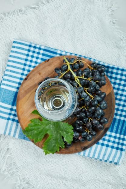 Een cluster van zwarte druiven met blad en een glas wijn op wit oppervlak met blauw tafelkleed Gratis Foto