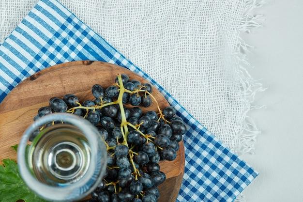Een cluster van zwarte druiven met blad en een glas wijn op witte ondergrond Gratis Foto
