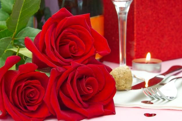 Een compositie van een mooi boeket rozen, glazen en een fles champagne creëert een romantische kaart of poster. het concept van valentijnsdag, moederdag, 8 maart. Premium Foto