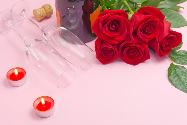 Een compositie van een mooi boeket rozen, kaarsen, glazen en een fles champagne zorgt voor een romantische kaart. het concept van valentijnsdag, moederdag, 8 maart. Premium Foto