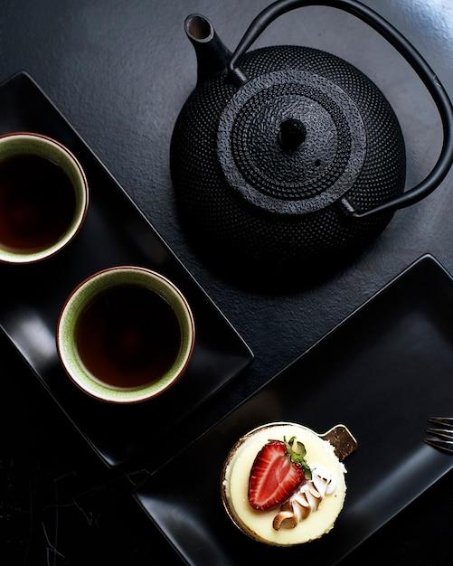 Een cupcake met room en aardbei, zwarte ketel en twee kopjes thee. Gratis Foto