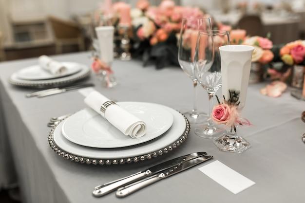 Een deel van de stijlvolle tafel instelling met bord en bestek. vlakbij ligt een wit visitekaartje. kopieer ruimte Premium Foto