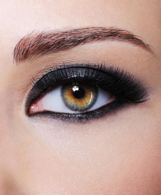 Een deel van het wijfje met oog met heldere zwarte glamoursamenstelling - macroschot Gratis Foto