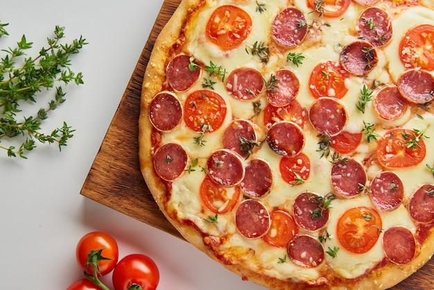 Een deel van hete zelfgemaakte italiaanse pepperonispizza met salami, mozzarella op witte lijst Premium Foto