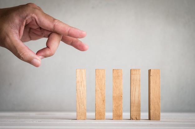 Een deel van menselijke vingerduw houten domino op lijst Premium Foto