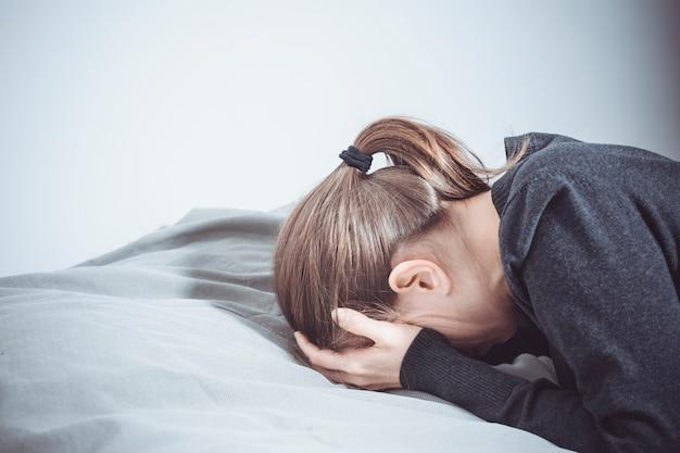 Een depressieve vrouw huilt met haar handen voor haar gezicht, liggend op de bank. Premium Foto