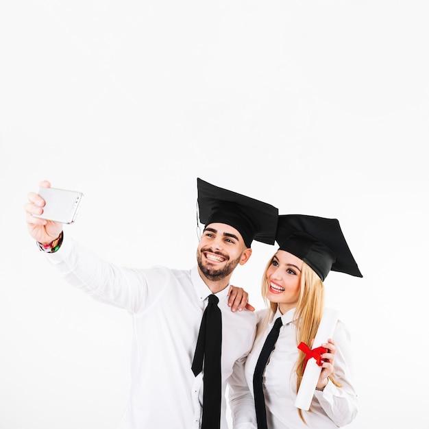 Een diploma behalend paar in mortarboards die selfie nemen Gratis Foto