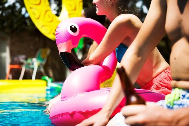 Een diverse groep vrienden die van de zomertijd genieten bij het zwembad met opblaasbare dobbers Gratis Foto