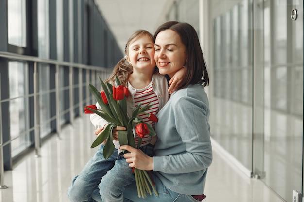 Een dochter geeft moeder een bos rode tulpen Gratis Foto