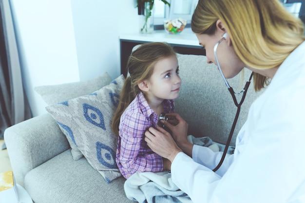 Een dokter kwam naar haar toe en luisterde met een stethoscoop naar haar Premium Foto