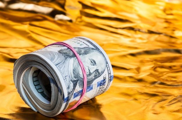Een dollarrolletje ligt op een gouden achtergrond. Premium Foto
