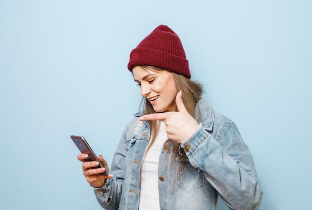Een donkerbruin meisje met een mobiele telefoon die zichzelf selfie en gelukkig maakt op een blauwe achtergrond Premium Foto
