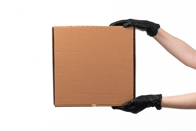 Een doos van de vooraanzichtlevering houdt door wijfje zwart handschoenen op wit bureau indient Gratis Foto