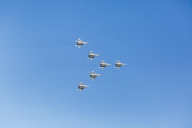Een driehoekige formatie van een groep van zes russische militaire straaljagers die hoog in de blauwe lucht vliegen Premium Foto