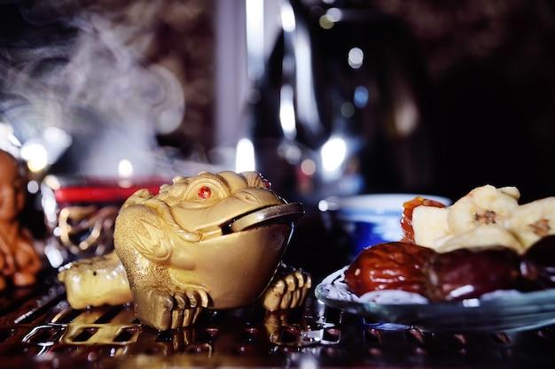 Een drietandige theepad met een munt in zijn mond is een symbool van rijkdom en welzijn. thee ceremonie Premium Foto