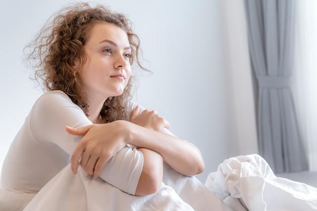 Een dromerig meisje zit in de slaapkamer, ze kijkt naar buiten en denkt aan iets. Premium Foto