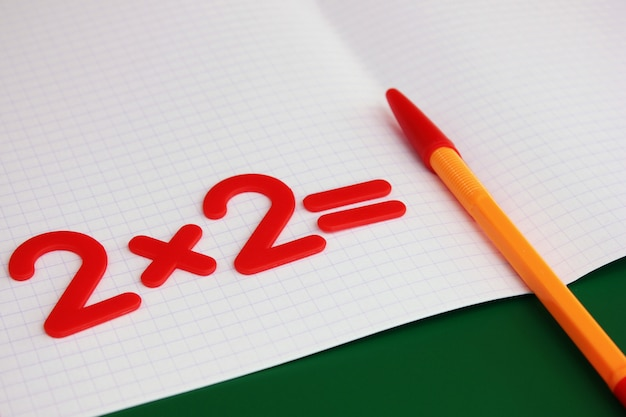 Een eenvoudig wiskundig voorbeeld in een schoon schoolnotitieboekje. terug naar school. Premium Foto