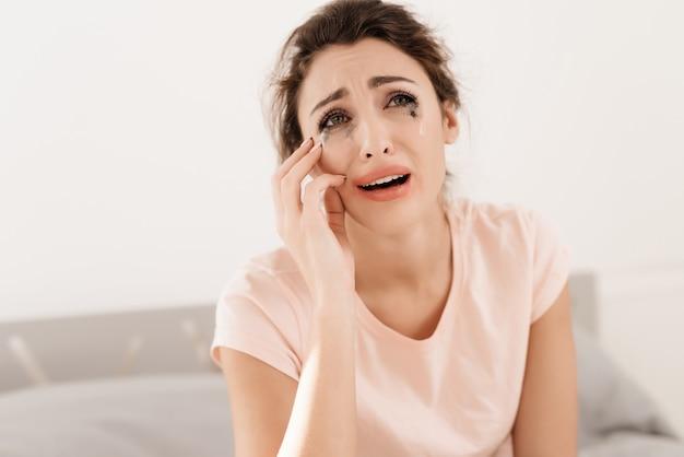 Een eenzame vrouw huilt alleen, haar mascara is gestroomd. Premium Foto