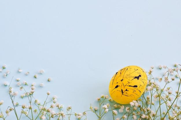Een ei is geel met zwarte vlekken en bloeit op een lichtblauwe achtergrond met een kopie van de ruimte. pasen. minimalisme. feestelijke achtergrond. ansichtkaart. kader Premium Foto