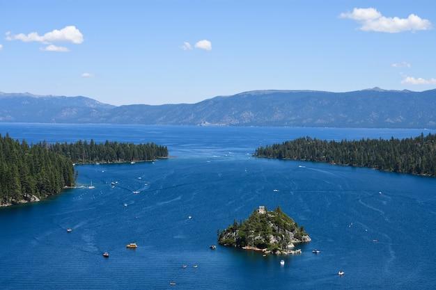 Een eiland dat in de oceaan wordt geïsoleerd, omringd door sparreneilanden en hoge rotsachtige bergen Gratis Foto
