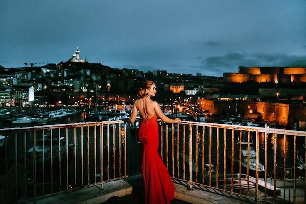 Een elegant meisje in een rode avondjurk in de straten van de nachtstad marseille. een vrouw in een rode avondjurk in frankrijk. Premium Foto