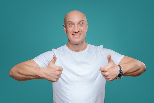 Een emotionele man in een wit t-shirt laat met een handgebaar zien dat alles cool is Premium Foto