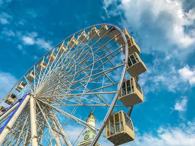Een enorm reuzenrad op blauwe hemel met wolken en een kerk met een gouden koepel. Premium Foto
