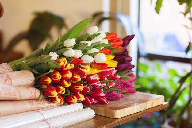 Een enorm veelkleurig boeket tulpen ligt op een tafel in een bloemenwinkel Premium Foto